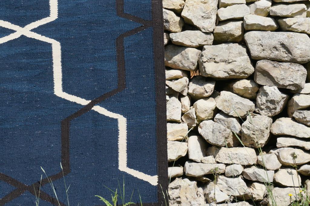 Kilim Arabesque Bleue photographié sur un mur de pierre dans l'île de ré.